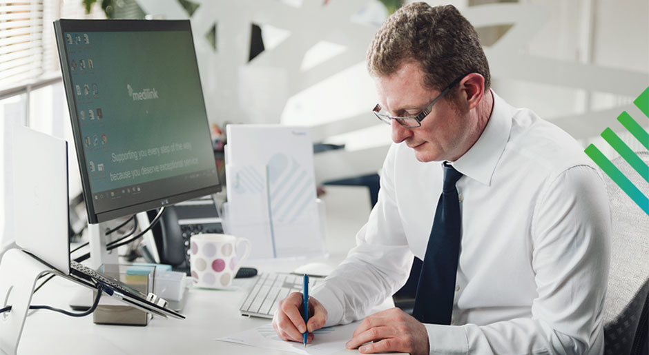 Man sat at desk writing
