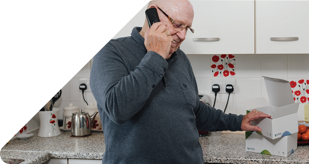 Man on phone in his kitchen with Medilink product